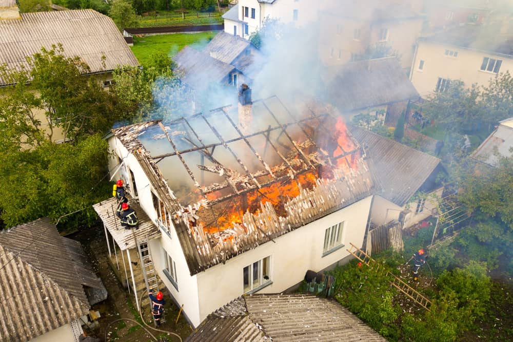 aerial view house fire with orange flames white thick smoke